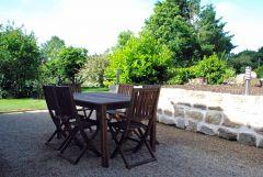 Terrasse avec salon de jardin en bois donnant sur le jardin exposé sud ouest